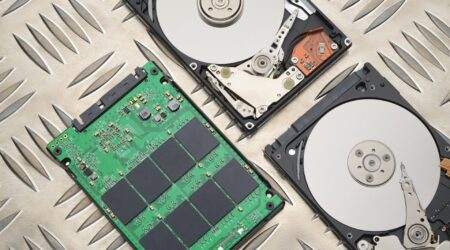 Open HDD and SSD disk drives on metal plate background